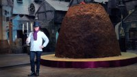 Heston Blumenthal stands by a giant Christmas cake